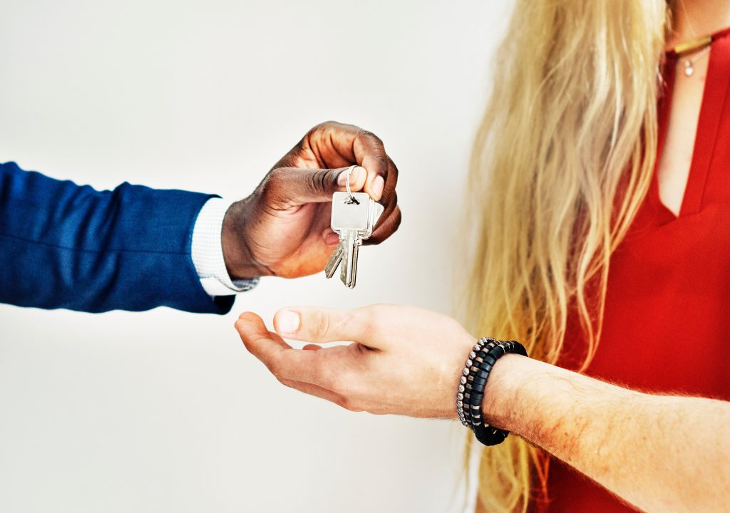 A realtor gives the house keys to the buyers as they sell their home at the right time.
