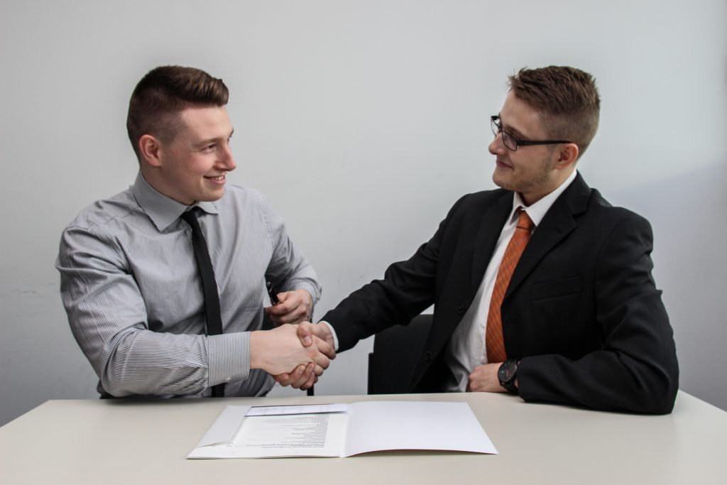 Two men sitting down and shaking hands after sealing the deal on a real estate transaction.