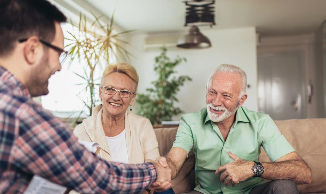 Older couple shaking the hand of their business partner