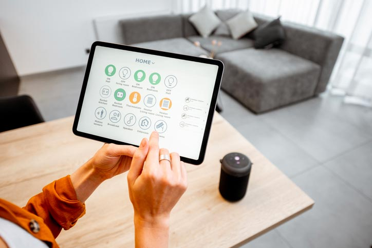 Third person perspective of woman using smart home app to control various smart home devices