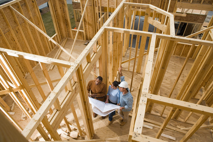 Couple inside early construction home with construction worker going over plans