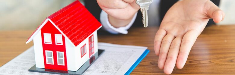 Real estate agent holding key in one hand and extending her other hand for a handshake
