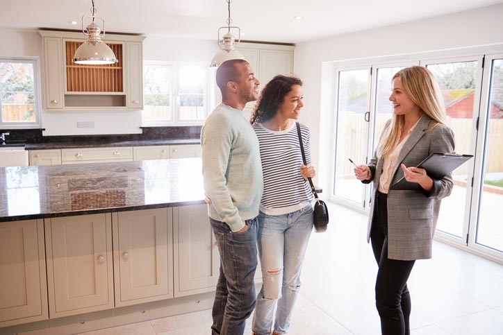 Couple talking with real estate agent in empty home